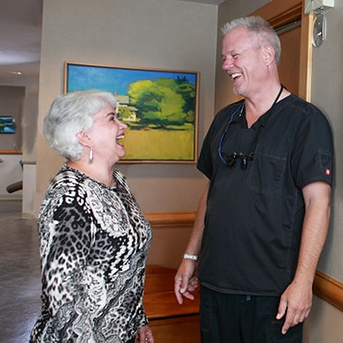 Dr. Aichlmayr laughing with one of his patients