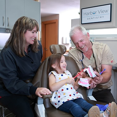 Dr. Aichlmayr teaching the importance of keeping your teeth cleaned with a child patient
