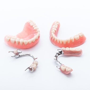 Different parts of dentures, including partial and full dentures