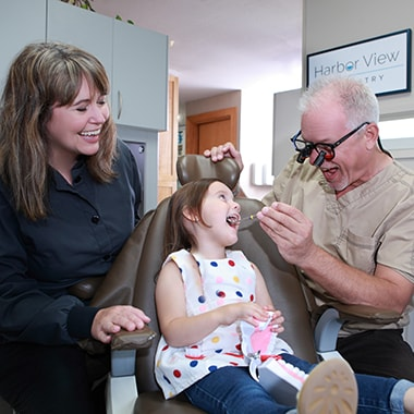Dr. Aichlmayr laughing with a young patient in the dental chair