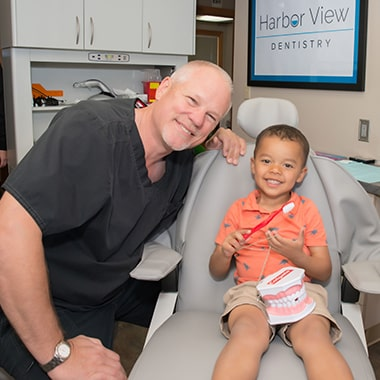 Our Gig Harbor dentist, Dr. Jim Aichlmayr and a little boy patient smiling in the dental chair